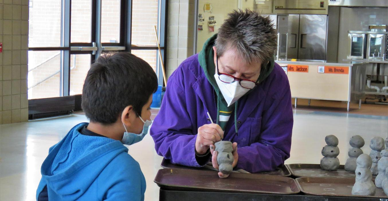 Lee art teacher helps put a students' name on a clay art project.