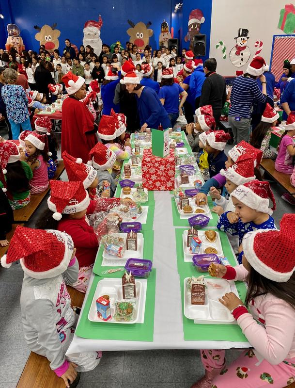 students on stage signing Christmas songs while other students wearing Christmas pj's and wearing Santa hats are eating breakfast