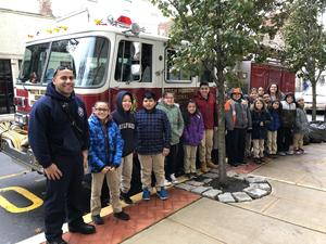 North Hudson Firefighter with a class of students and their teacher in front of the fire engine