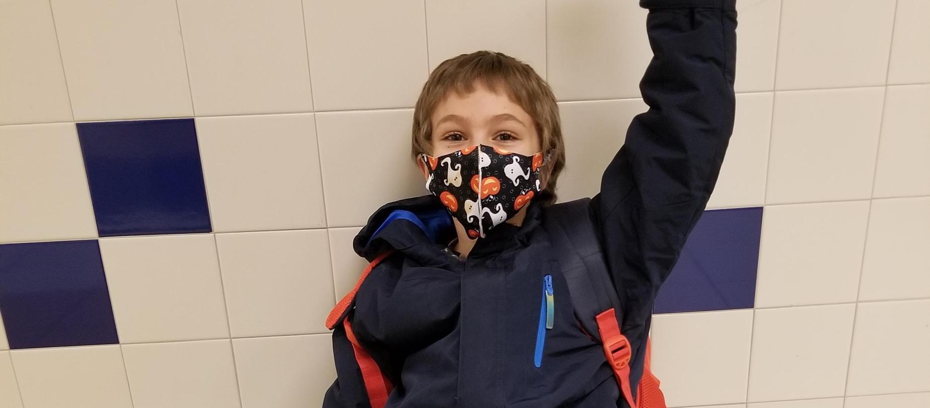 boy sitting on the floor wearing a mask