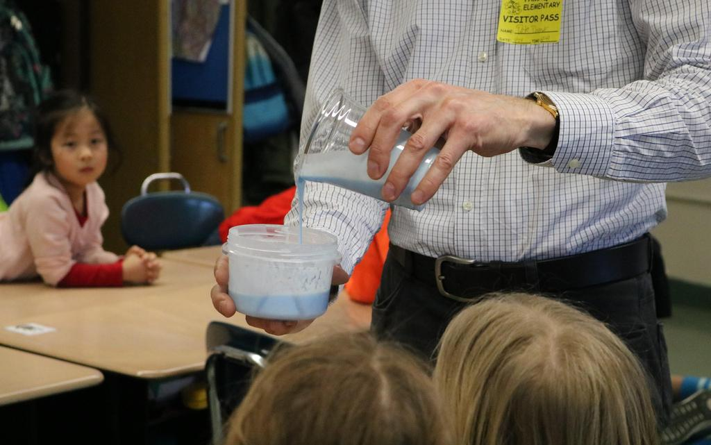 Photo of Tamaques parent teaching students the chemistry of slime during STEAM Day.  Close of his hand pouring slime, as student looks on.