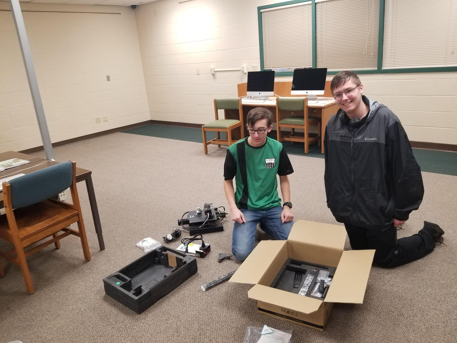 Two boys kneeling on the floor by a box with electronic parts around them