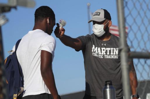 Coach takes temperature of athlete
