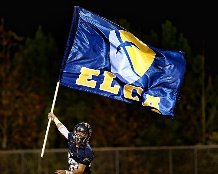ELCA Football Player running with ELCA Flag