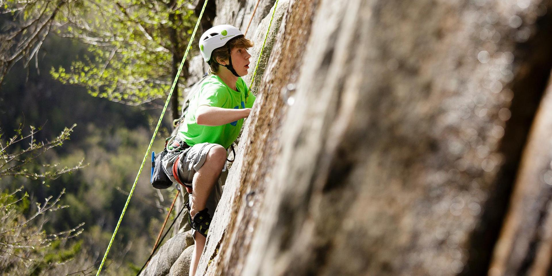 A student climbing a cliff wall.