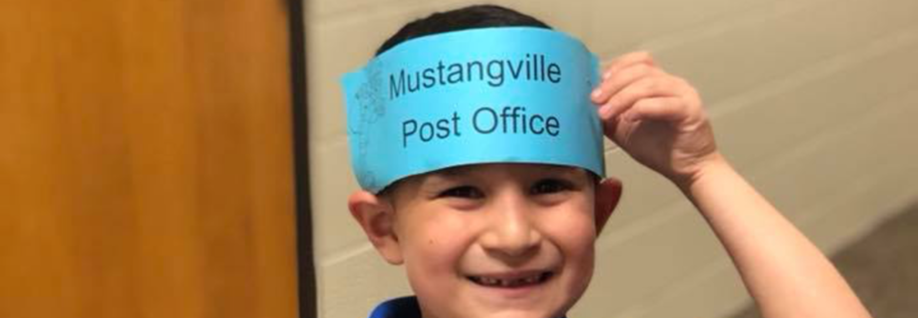 boy with Mustangville Post Office cap