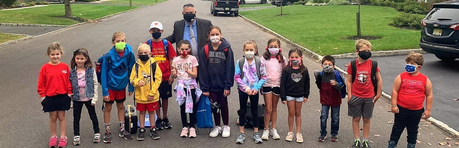 Photo of superintendent posing with students on Walk to School Day