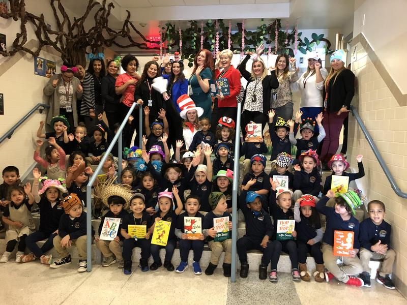 group photo of kindergartners with teachers, aides, and Hudson Administration in the front entryway of the school making funny faces