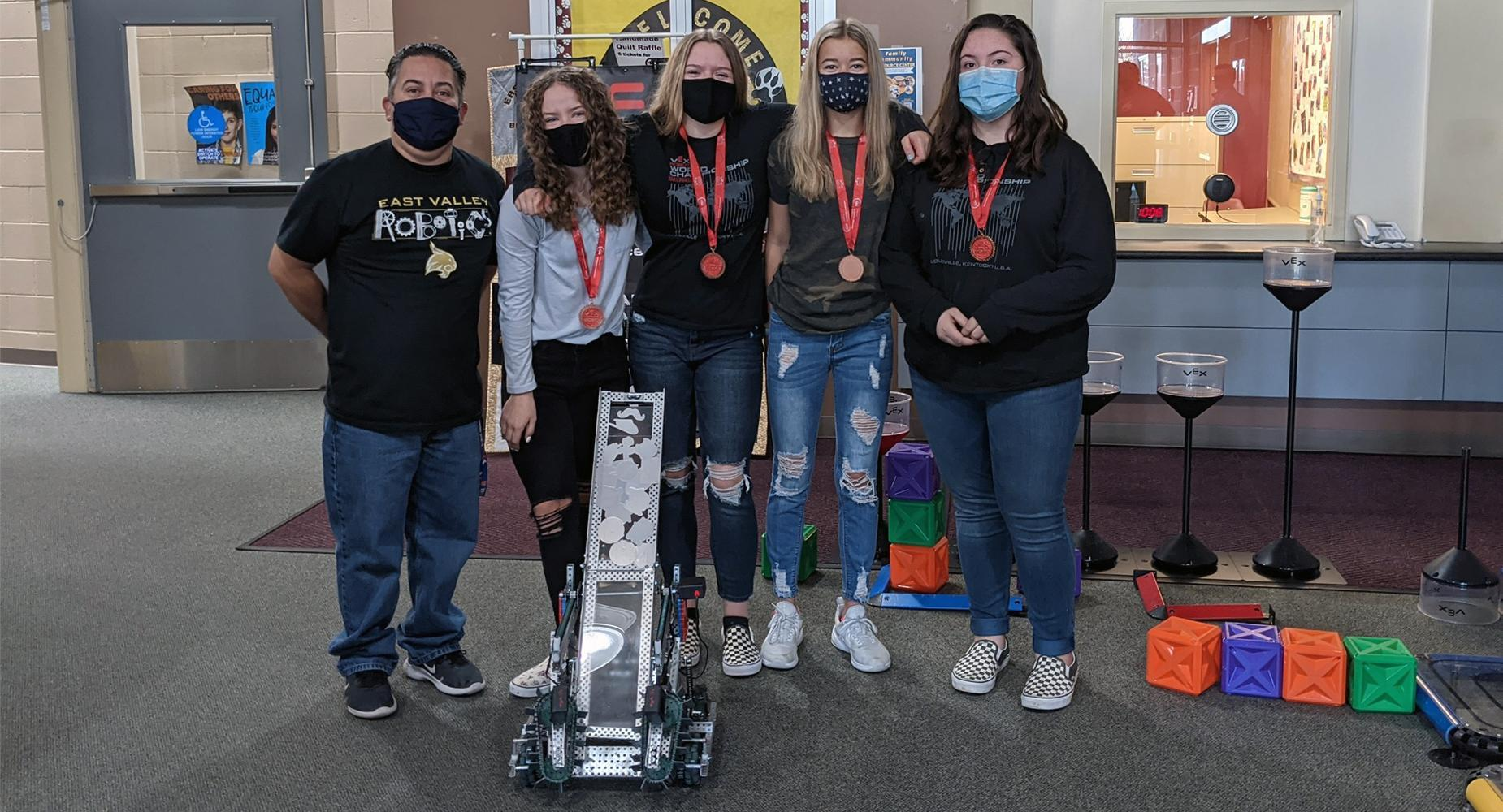 East Valley Robotics Advisor Jesus Gomez poses with Ashley Wyne, Aryn Okelberry, Bailey St. Peter, Aleiah Downing, and their winning robot.