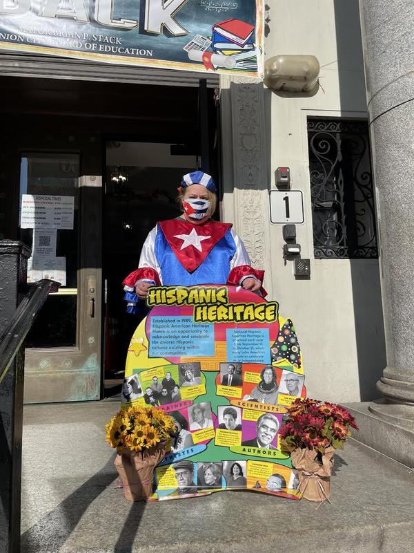 Woman in Cuban flag outfit holding Hispanic Heritage poster outside