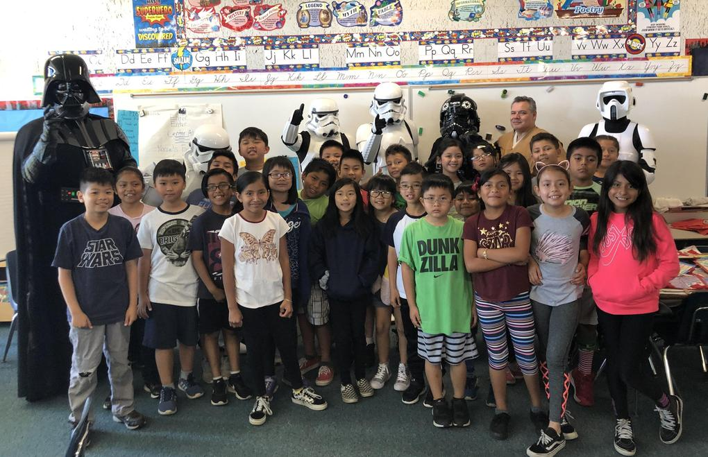 Star Wars characters stand with students.