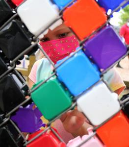 Photo of playground mosaic with student's face on other side of fence.