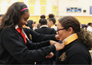 One teenage girl helping another tie a tie around her neck tie