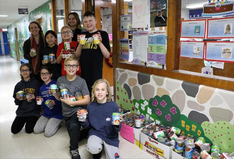 Photo of Jefferson students and staff with boxes of non-perishable items collected during annual
