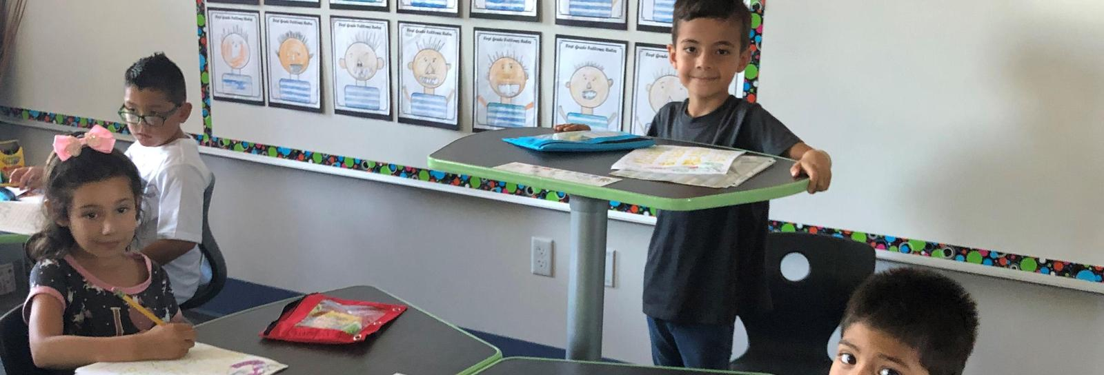 A Roosevelt student chooses to complete his classwork standing up. Adjustable student desks offer our scholars alternatives to traditional learning.