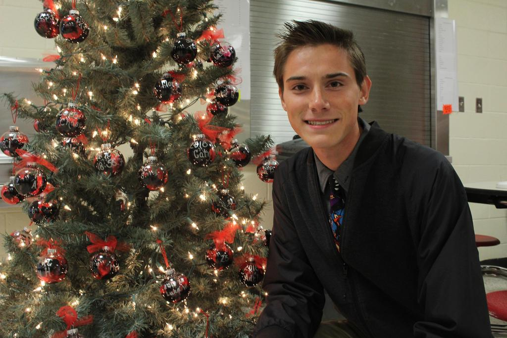 Student in front of a Christmas tree