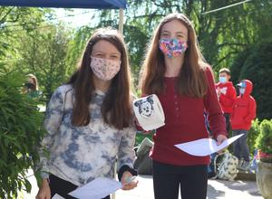 Roosevelt 6th graders Whitney Crooks (left) and Scarlett Goldman hold pandemic-related items to place in a school time capsule as part of a social studies unit on primary and secondary sources.
