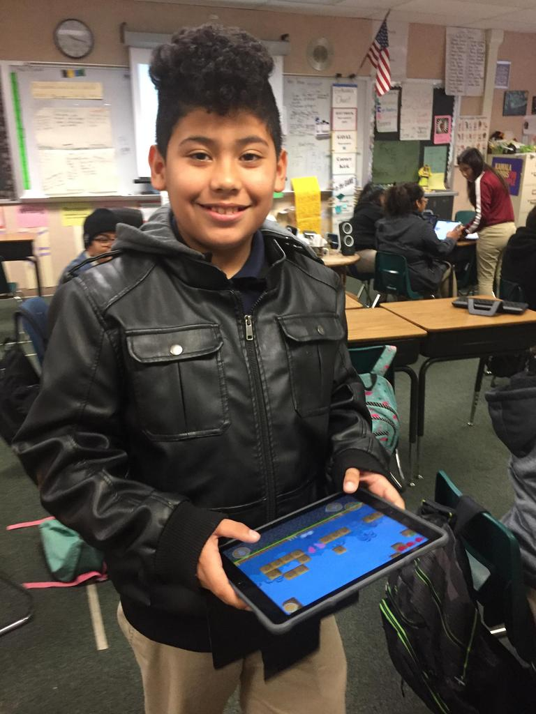 Student smiles while holding iPad that he's using to code