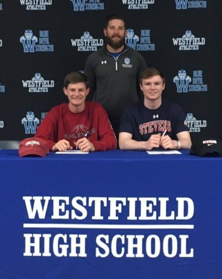 Westfield High School Basketball Coach James McKeon joins student-athletes as they sign Letters of Intent to play basketball at the college level.  From left, Thomas McGuire – Muhlenberg College and Matthew Crowley – Stevens Institute of Technology.