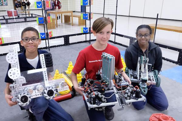Students holding robots they created.