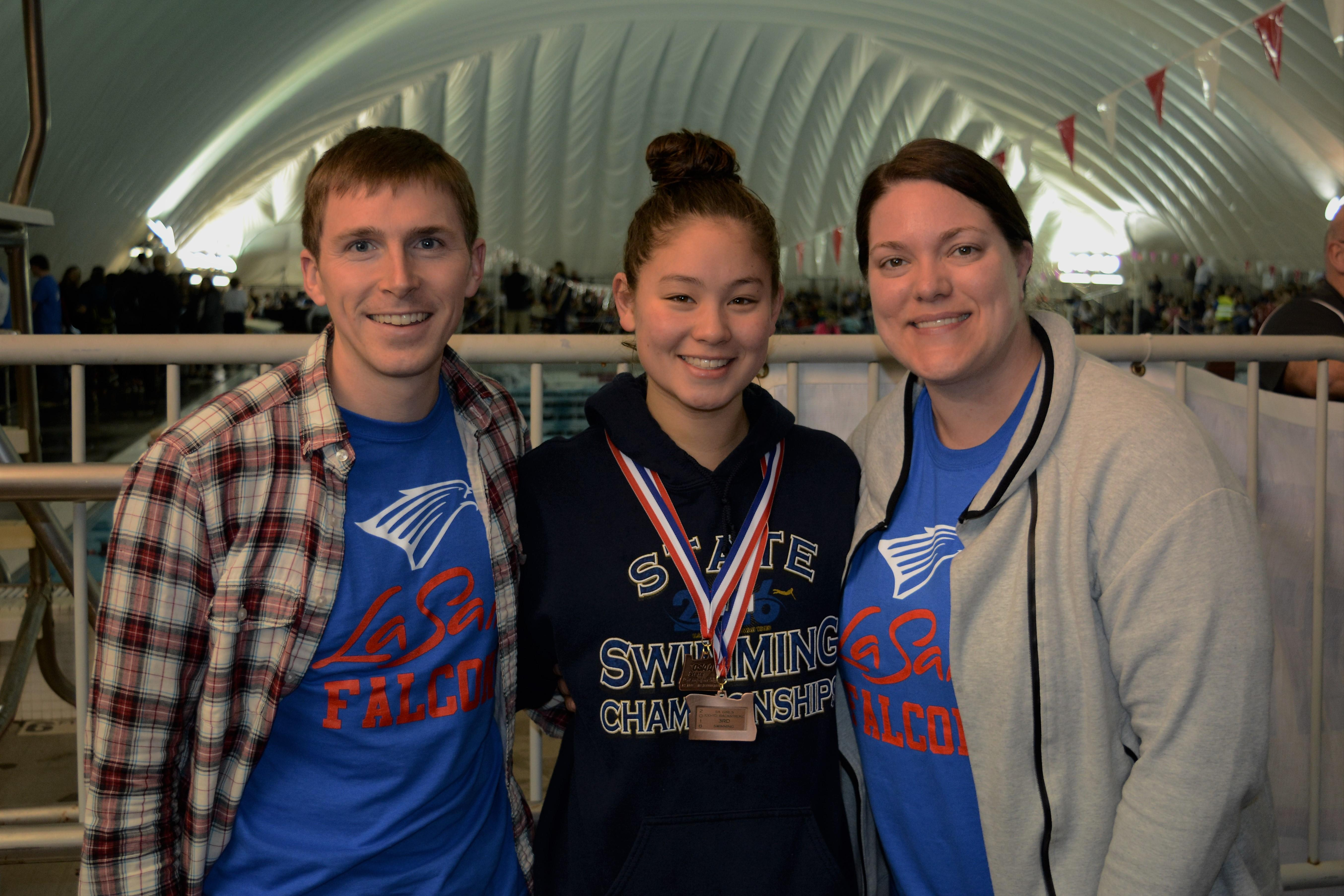 Swimmer with coaches and state medals
