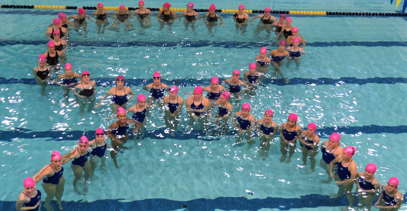 TK-DK-Hastings swim team members form the cancer ribbon logo during their annual swim against cancer meet.