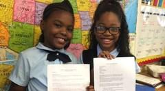 Two DEAW girls displaying their schoolwork