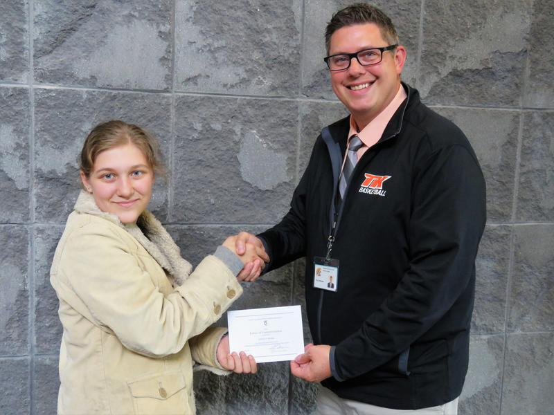 TKHS senior Kaylyn Beard receives a certificate from high school principal Tony Petersen recognizing her as a National Merit Scholarship Commended Student.
