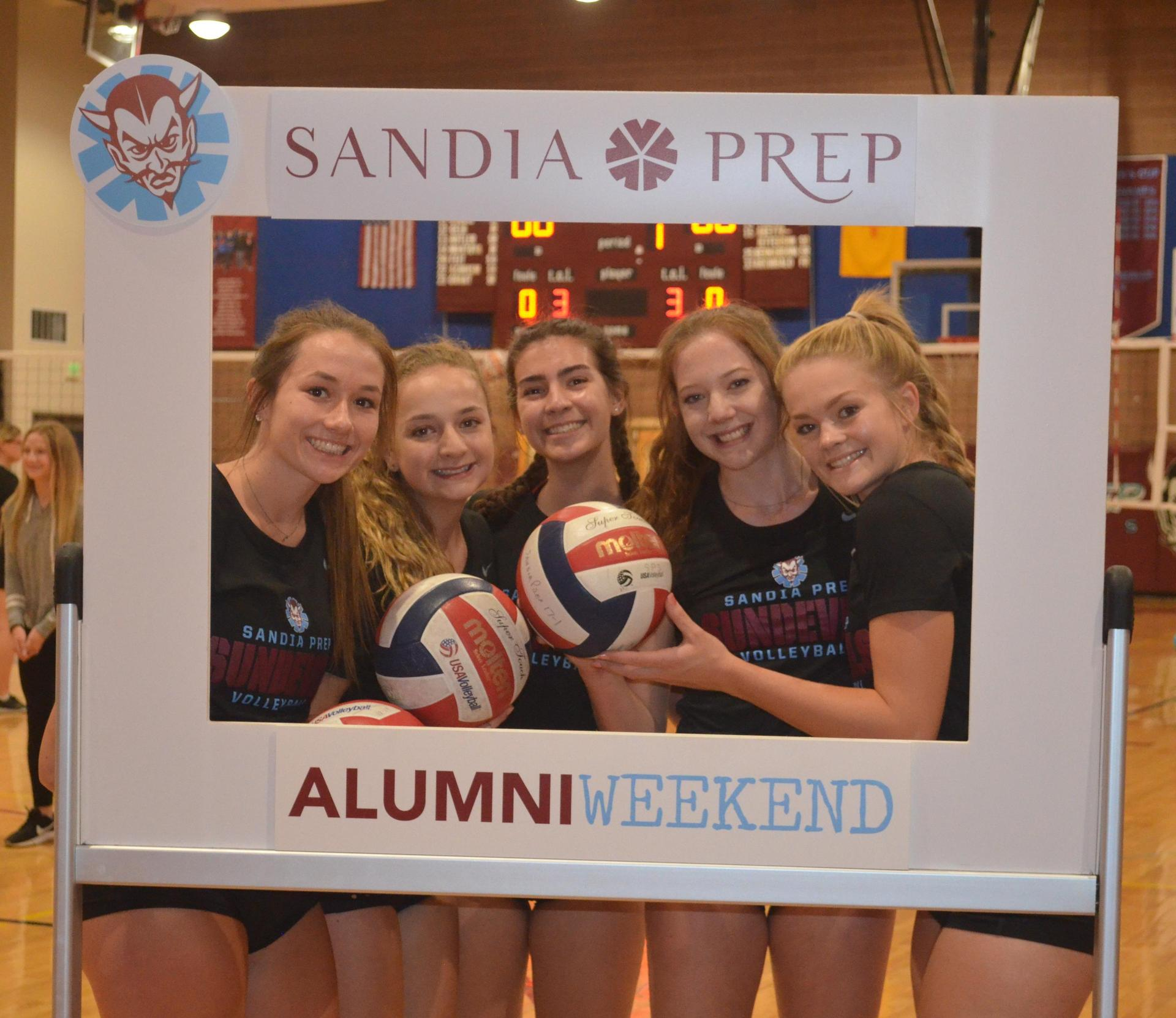 Students hold volleyballs and smile in event frame