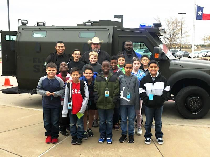 uniformed officers pose with group of students in front of emergency vehicle