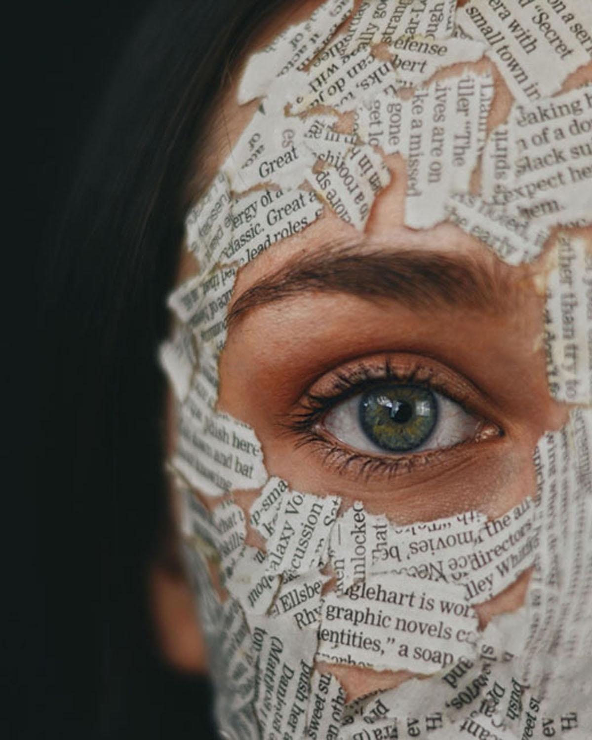 close up with eye surrounded by newspaper clippings