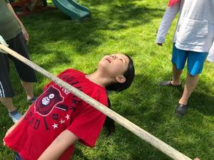 Photo of student doing limbo in backyard Field Day.