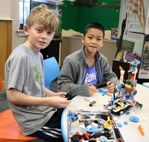 Wilson School 4th graders Dylan Dwan (left) and Aidan Liu build and program a Lego robot during an afterschool STEAM session.