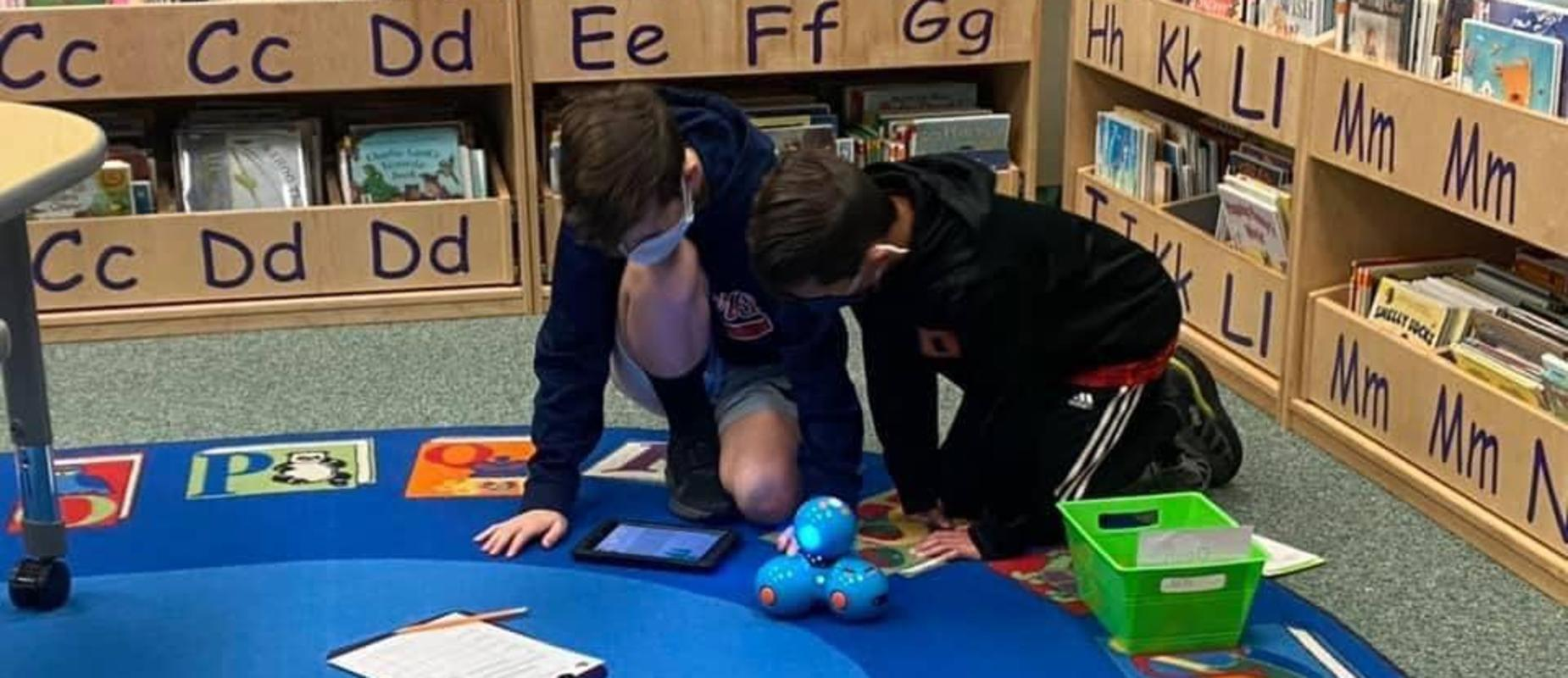 Two students coding a robot with an iPad