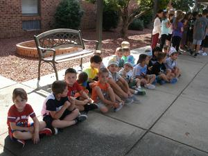 Students on the sidewalk are practicing for dismissal.