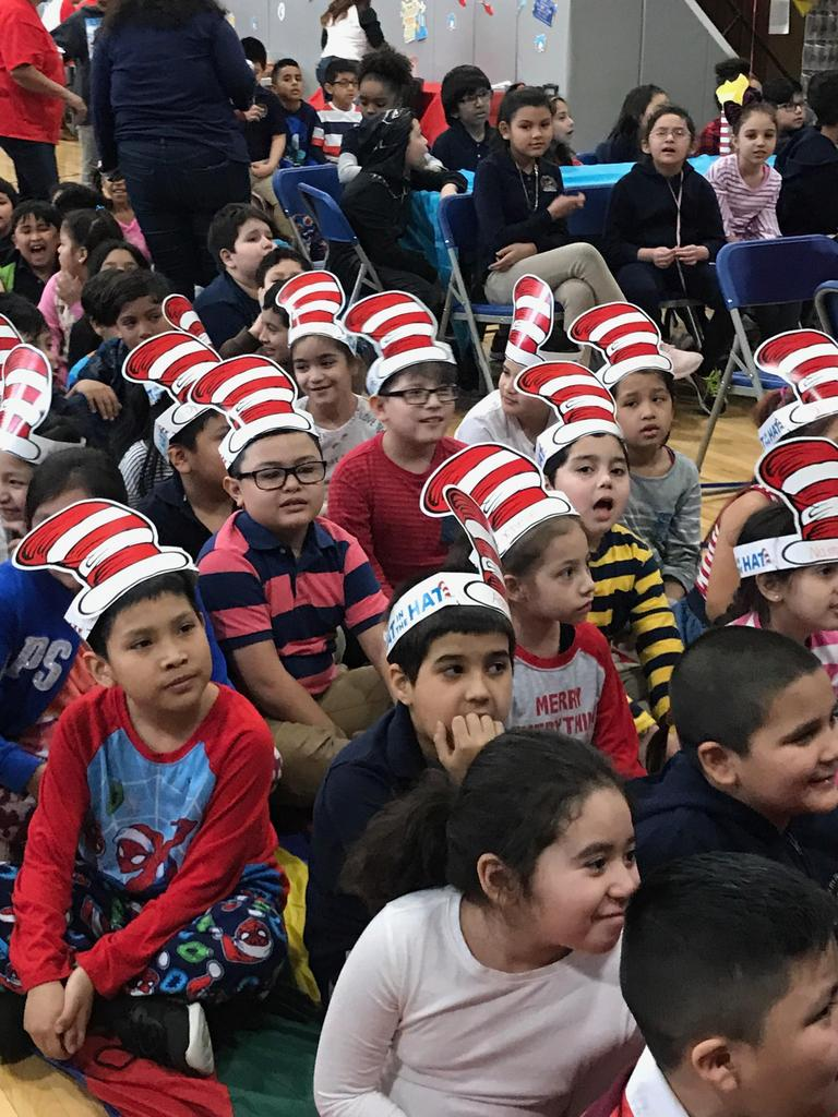 children sitting with their cat in the hat paper hats