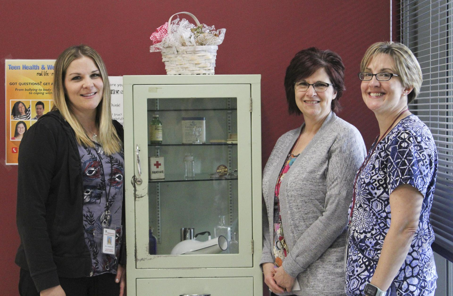 Three nurses at Naugatuck High School in front of historic nursing equipment