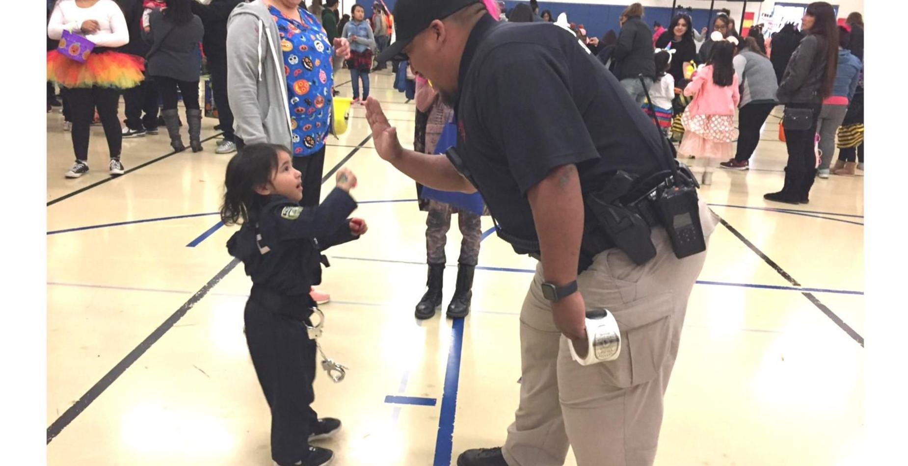a young child dressed up as a police officer giving  a high five to our school district onsite officer