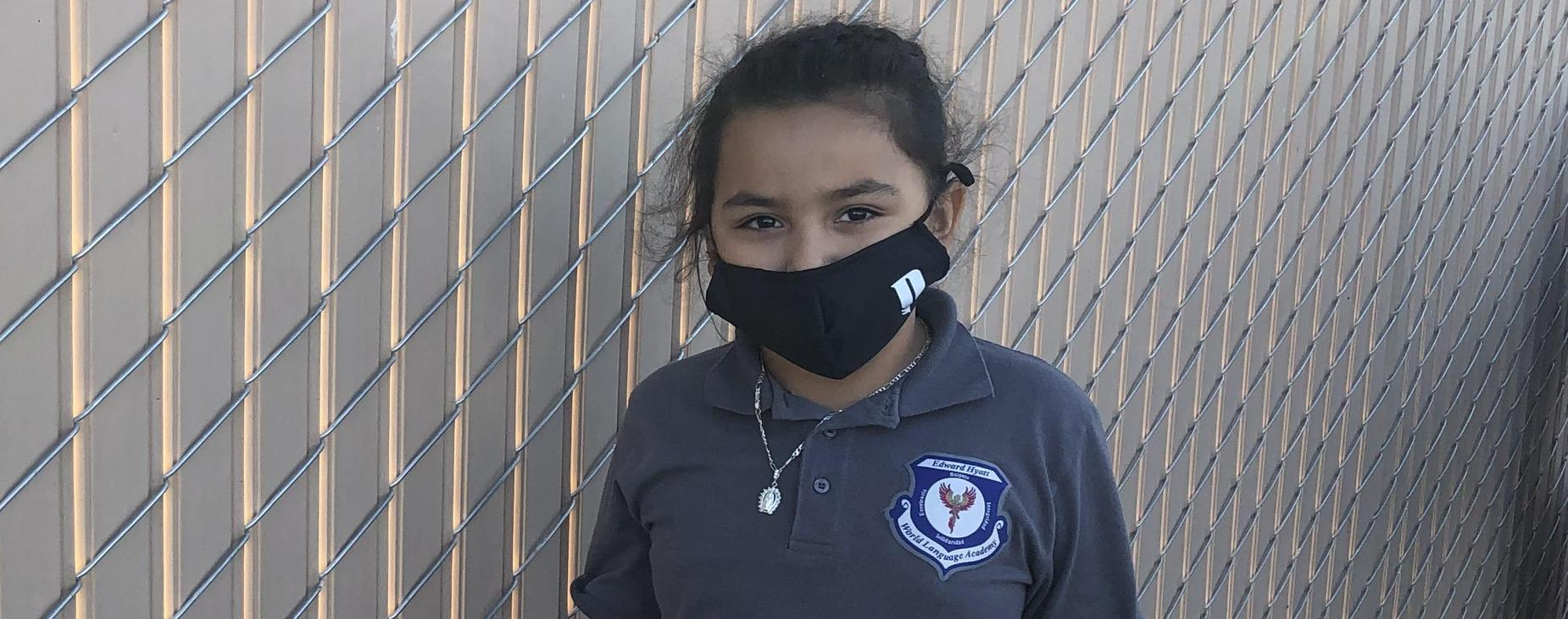 student with mask on in uniform polo