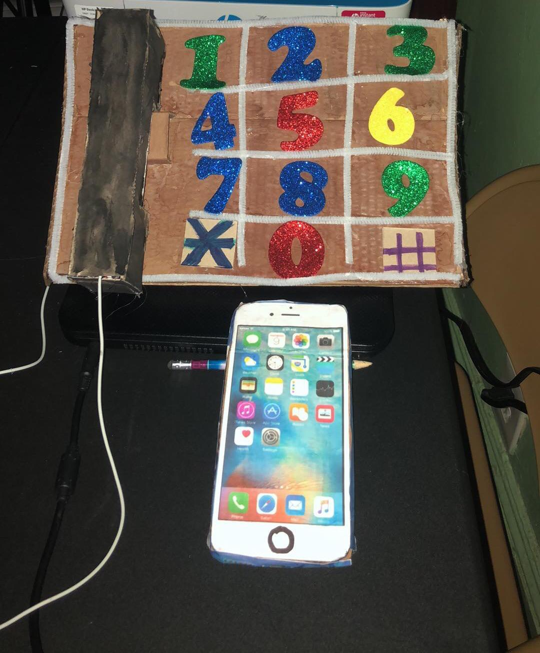 cardboard wall phone next to cell phone