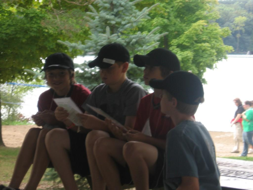 boys with caps on look at paper outside