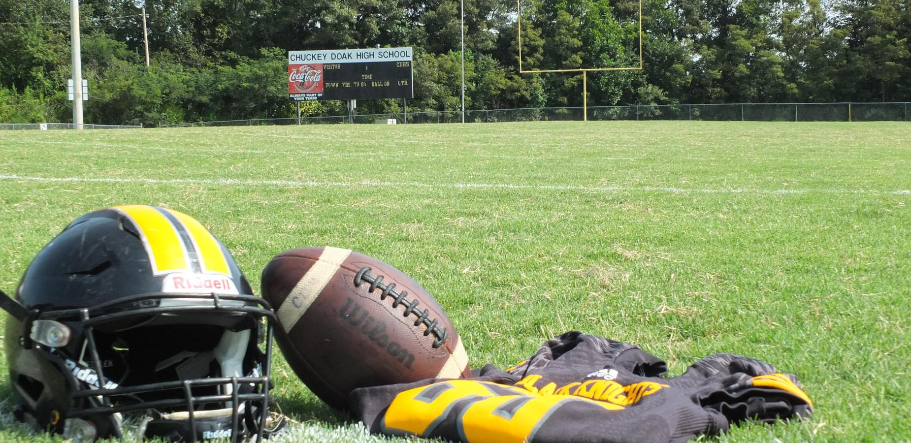 Chuckey Doak football helmet, jersey, and football on the football field