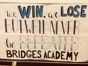 Sign hung in gym at Bridges Academy. It reads,