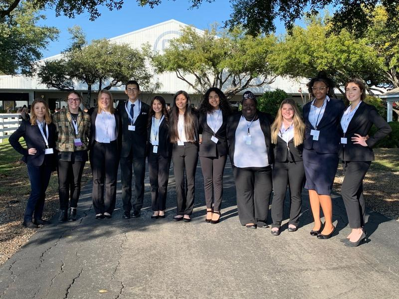 11 future health professional students in suits pose together at competition