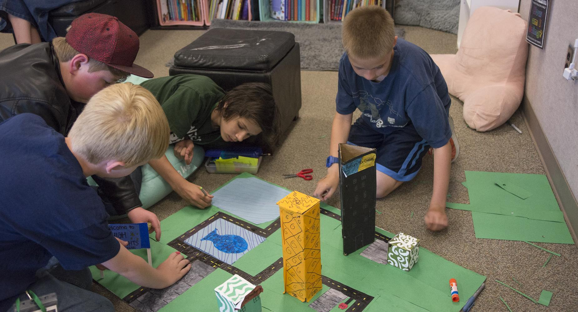 Four boys work on project on floor of classroom