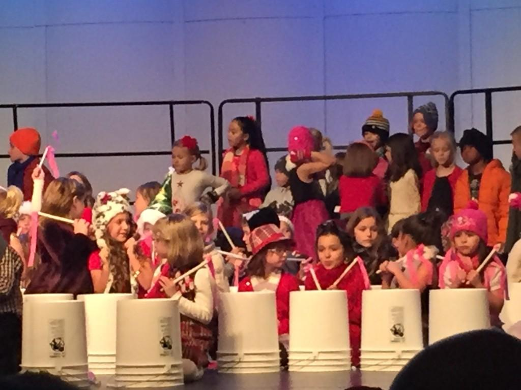 kids play drums on stage with buckets