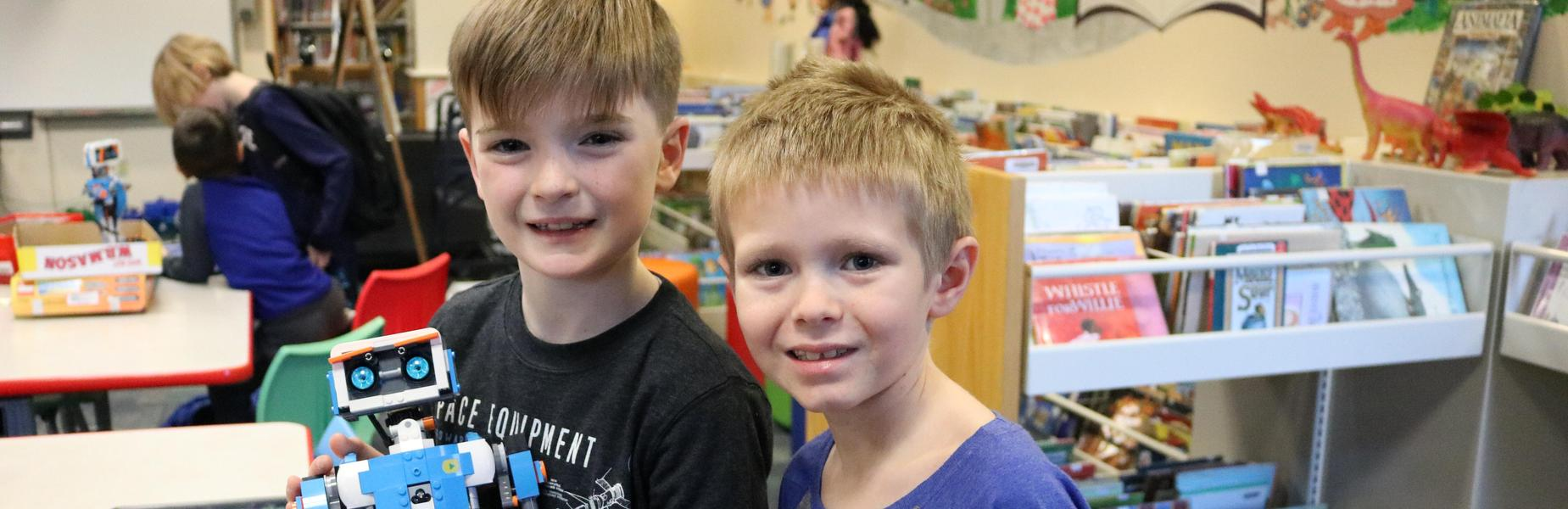 Two Wilson 3rd graders show off the robot they built and programmed during an afterschool STEAM session.