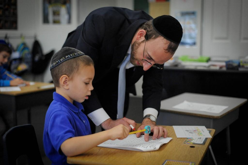 Rabbi Tesser helping a student with a worksheet