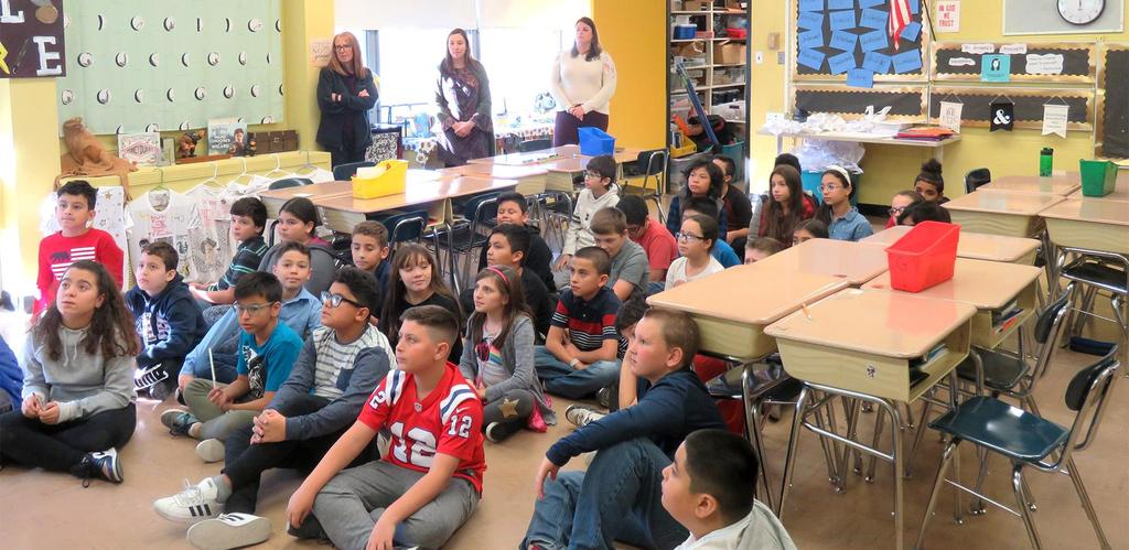 Webster School fifth graders, seated on the floor of a classroom, listen to meteorologist Kelly Ann Cicalese, who isn't pictured