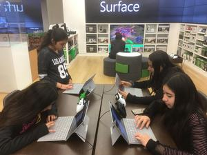 four girls working on laptop computers